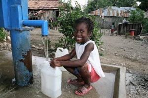 Ein Kind lässt Wasser aus einem öffentlichen Wasserpumpe in einen Kanister laufen. (Quelle: Jürgen Schübelin)