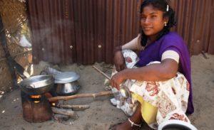 Eine Frau kocht auf einem kleinen Holzofen. (Quelle: Jens Großmann)