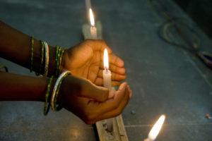 2 Hände schützen eine Kerzenflamme. (Quelle: Frank Rothe)